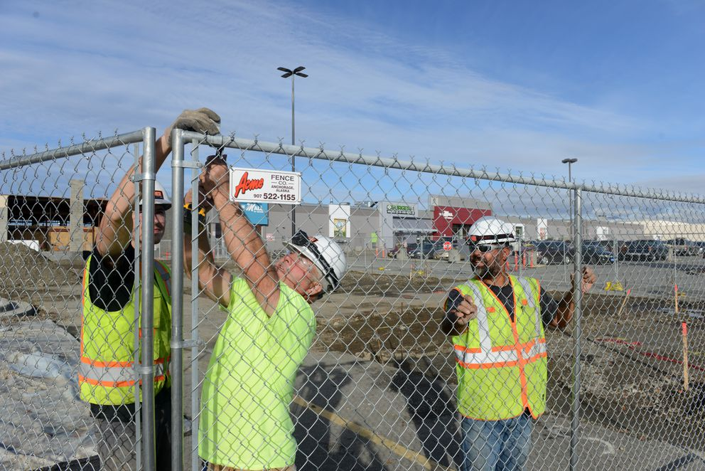 Garrett Fleener, Mike Bass and Mauro Miranda, with Bauer Construction, install a section of fence at the Midtown Mall. (Bob Hallinen / ADN)