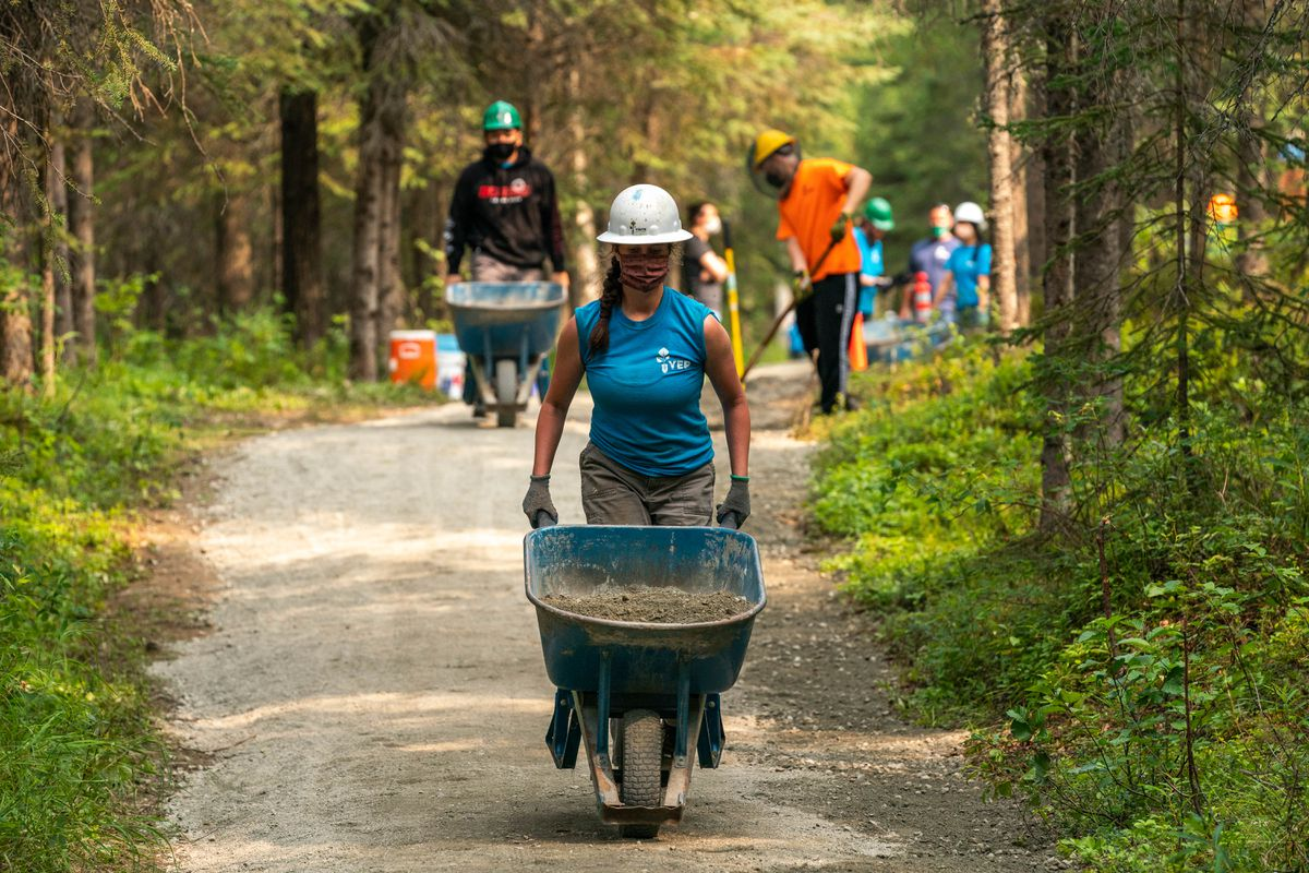 Alaska Middle College graduate Shannon Luna, 18, moves gravel into position on the Tour of Anchorage trail on Wednesday in Far North Bicentennial Park. (Loren Holmes / ADN)
