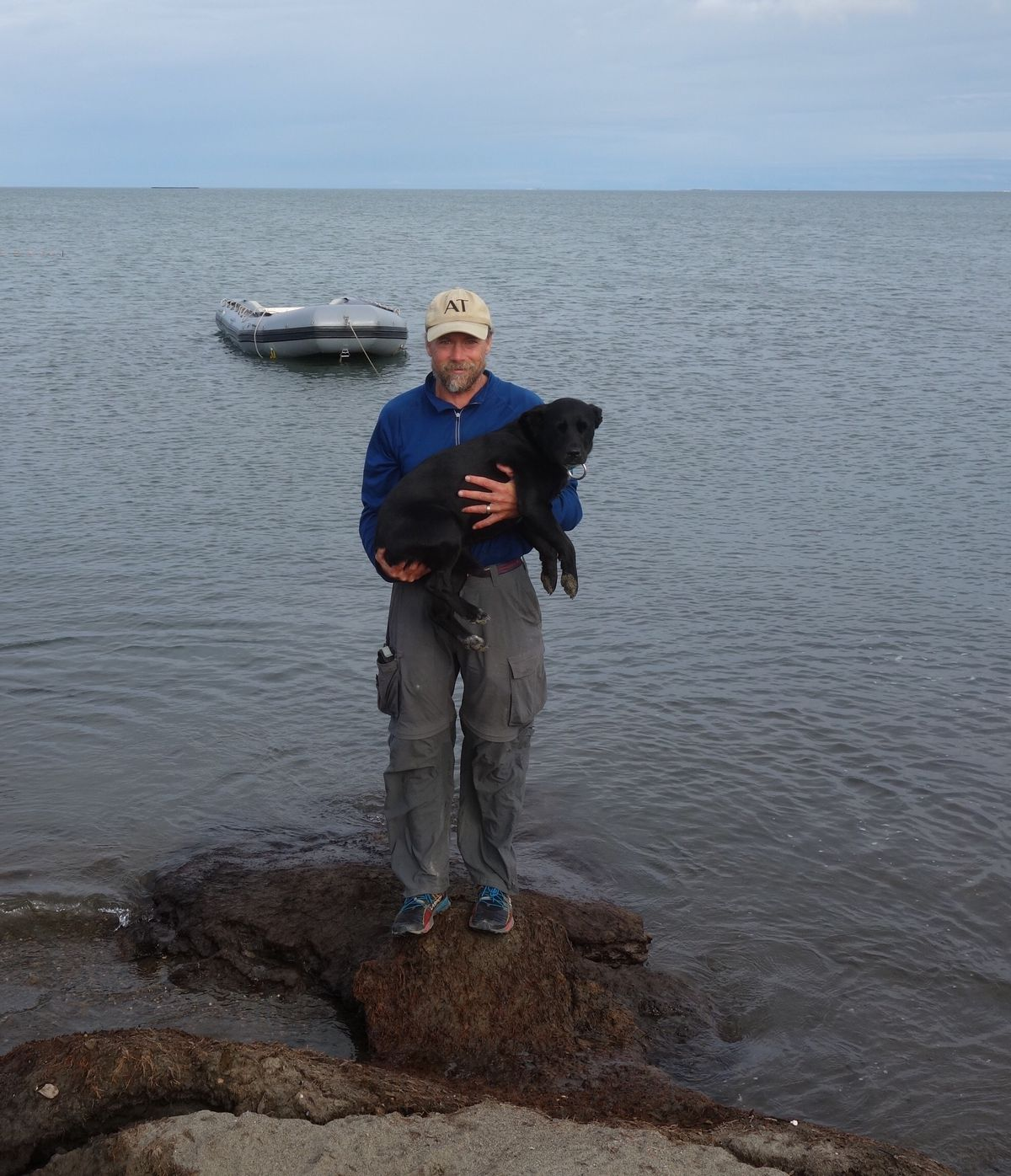 Ned Rozell and his dog Cora with the Arctic Ocean and Prudhoe Bay in the background on the day they finished their trans-Alaska hike. (Becky Baird)
