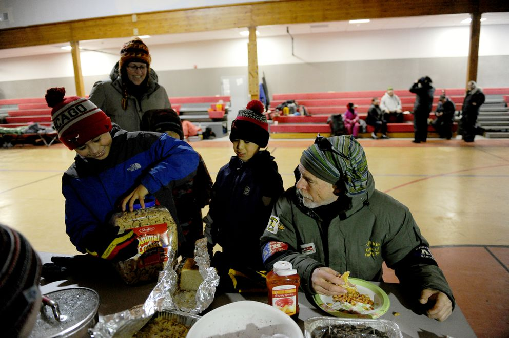 Iditarod musher Jeff King watches a village kids open a container of animal crackersKing brought as gift for the village to share at the Nulato checkpoint during the 2017 Iditarod Trail Sled Dog Race on Sunday, March 12, 2017. (Bob Hallinen / Alaska Dispatch News)