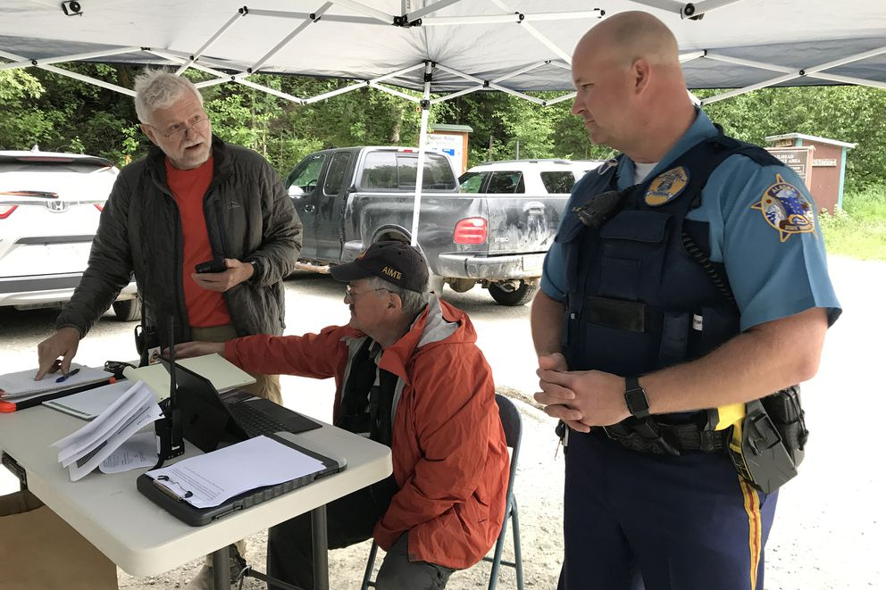 From left, Bill Laxson with Alaska Mountain Rescue Group, Tom Plawman of the Alaska Incident Management Team, and Alaska State Trooper Lt. Brent Johnson talk at the search base in parking lot of Pioneer Ridge Trail on Wednesday as the search continued for a missing hiker who reportedly encountered bears early Tuesday. (Bill Roth / ADN)