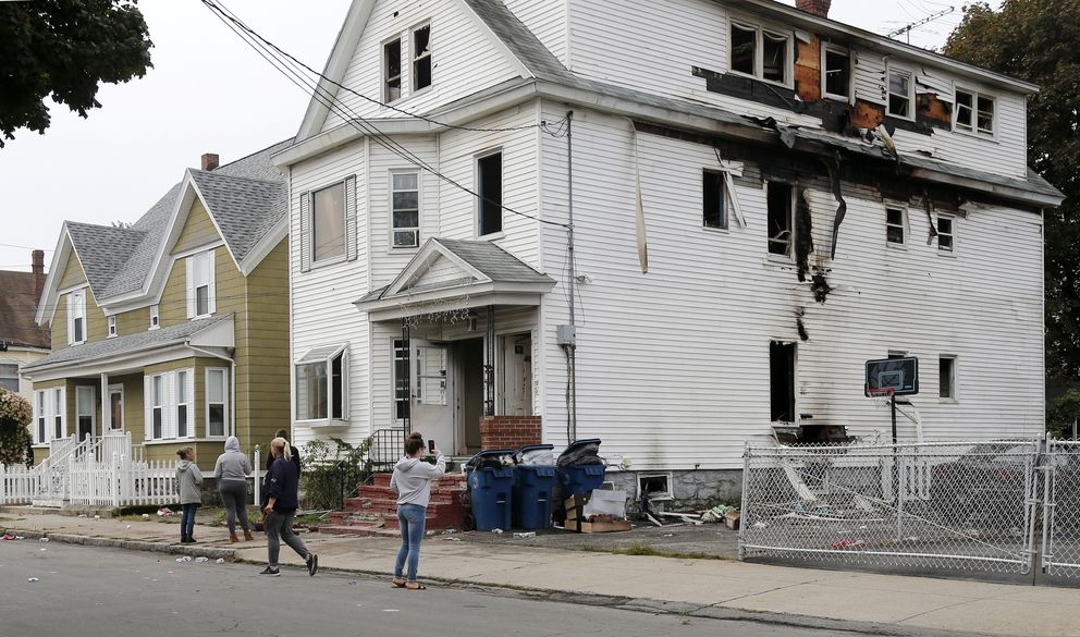 Lawrence residents stop to take photos of a house on Bowdoin Street in Lawrence Mass., Friday, Sept. 14, 2018. The home was one of multiple houses that went up in flames on Thursday afternoon after gas explosions and fires triggered by a problem with a gas line that feeds homes in several communities north of Boston (AP Photo/Mary Schwalm)