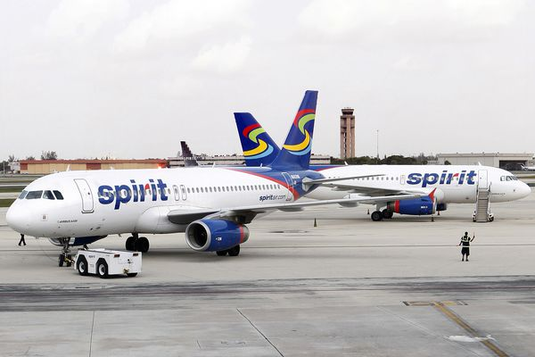 A member of Spirit Airlines grounds crew, right, guides a jet toward the runway at Fort Lauderdale-Hollywood International Airport in Florida on July 1, 2011. (Marsha Halper/Miami Herald/MCT)