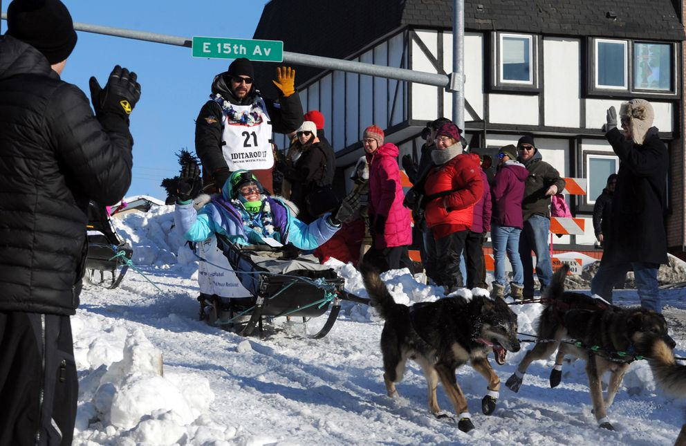 Richie Diehl of Aniak and Iditarider Liz Thomas exchange greetings with fans as they head down the Cordova Street hill during the 2017 Iditarod. (Erik Hill / ADN)