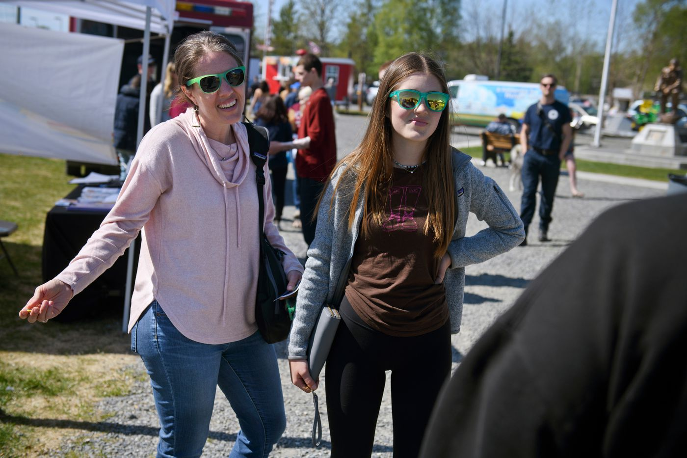 Anne Zink and her 13-year-old daughter, Lily, speak with passers-by at the Kenai Public Health Center's vaccine booth at the Wednesday Market in Soldotna. (Marc Lester / ADN)