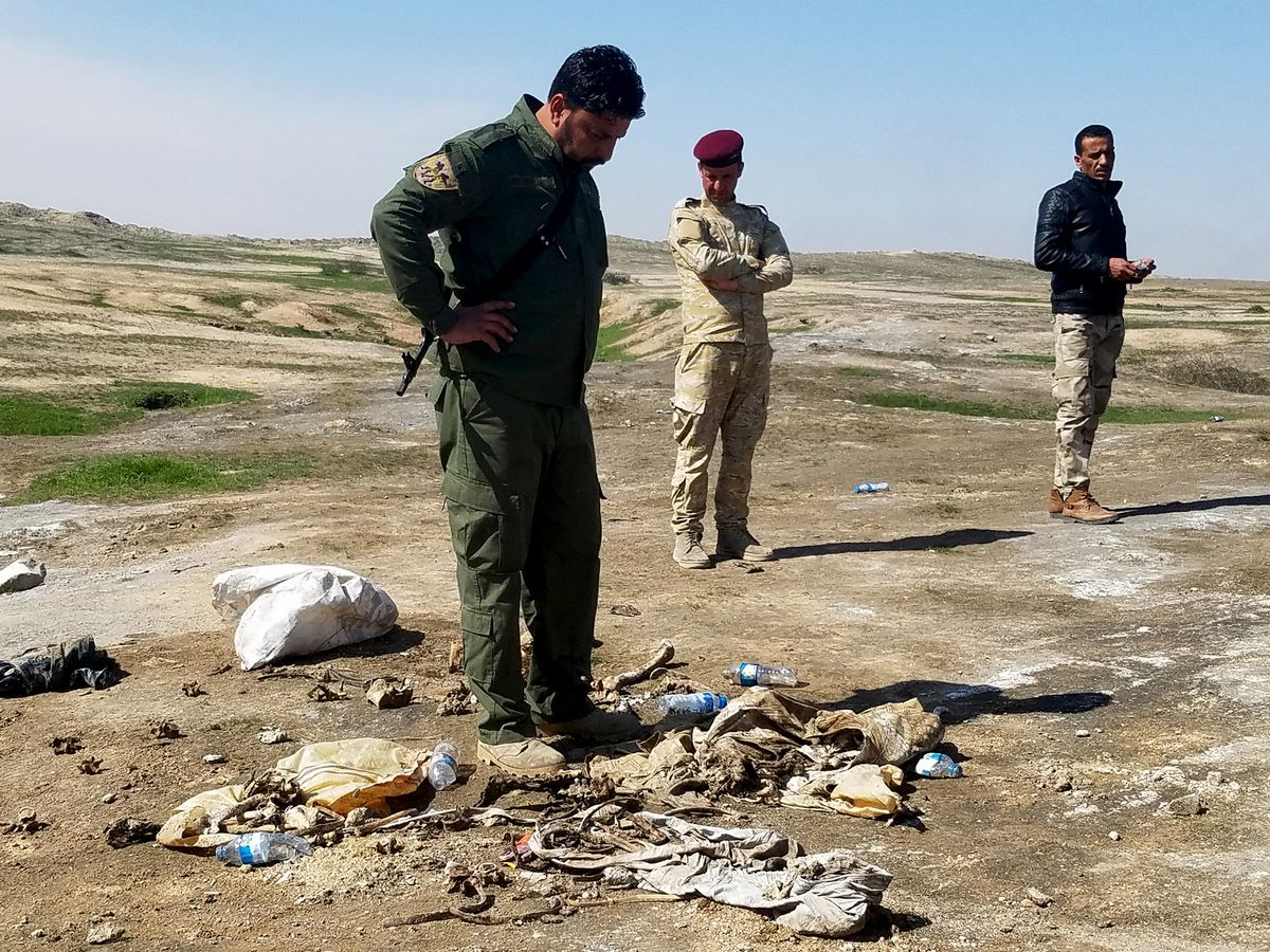 Sunni militia member Sgt. Major Yasser Ahmed, left, fellow militia members Captain Omar Hasan, center, and Salam Khalaf survey remains at a mass grave created by Islamic State outside his village south of Mosul on March 9. (Molly Hennessy-Fiske/Los Angeles Times/TNS)