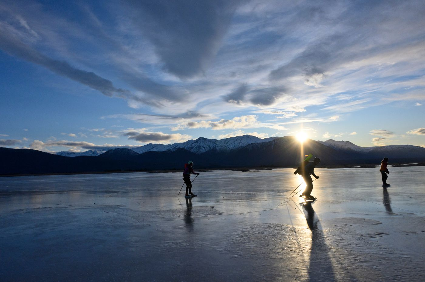 Skaters enjoy frozen lagoons on the Palmer Hay Flats State Game Refuge as the sun peeks over the mountain ridges. From left are Zoe Copp, Jason Copp and Britta Sonerholm. (Marc Lester / ADN)
