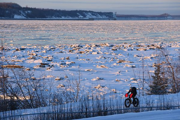 A bicyclist rides along the Tony Knowles Coastal Trail on Thursday, Feb. 4, 2021. Port MacKenzie is visible in the distance beyond the pan ice in upper Cook Inlet. (Bill Roth / ADN)
