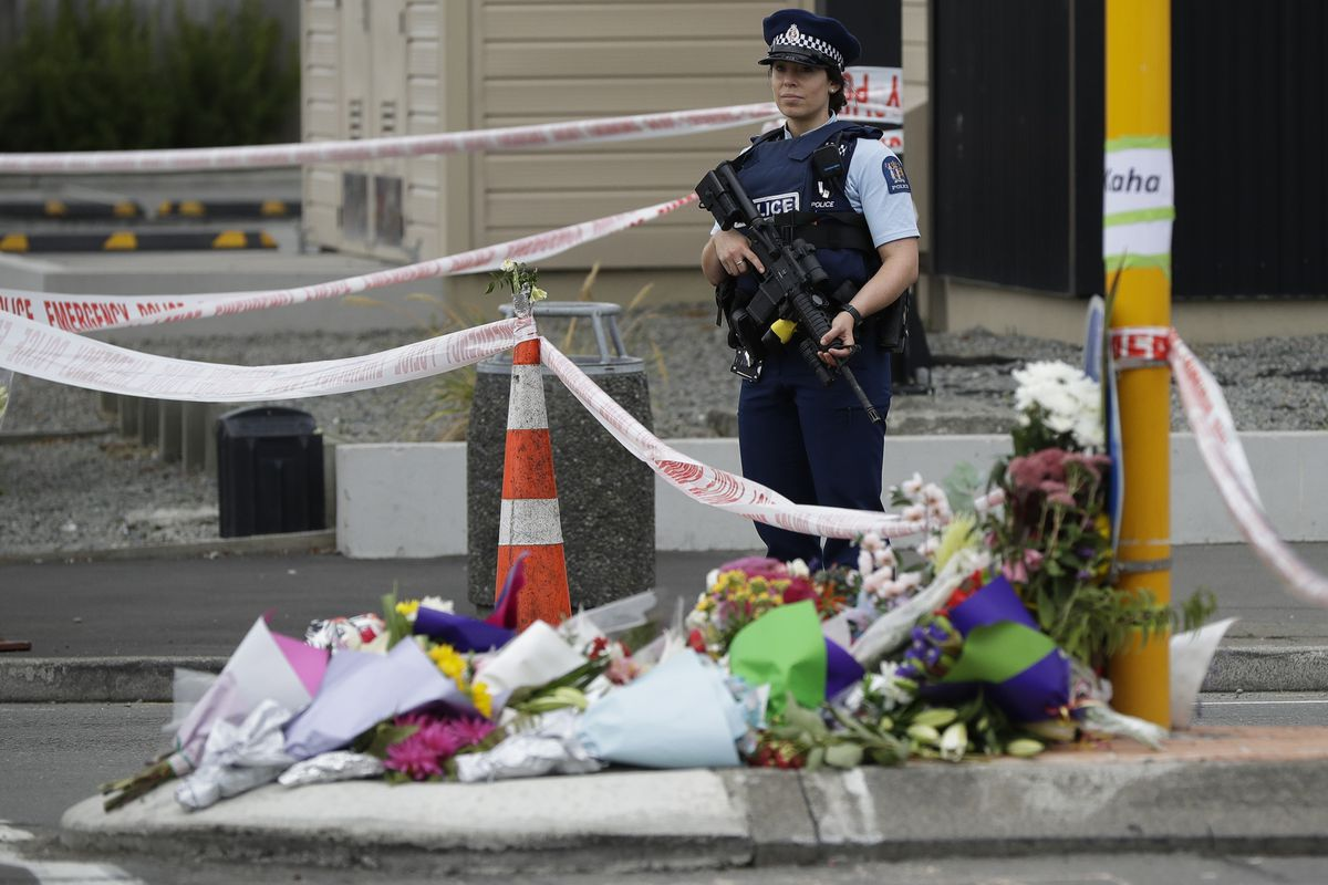 Police stand by makeshift memorial near the Linwood Mosque in Christchurch, New Zealand, Saturday, March 16, 2019, where one of the two mass shootings occurred. (AP Photo/Mark Baker)
