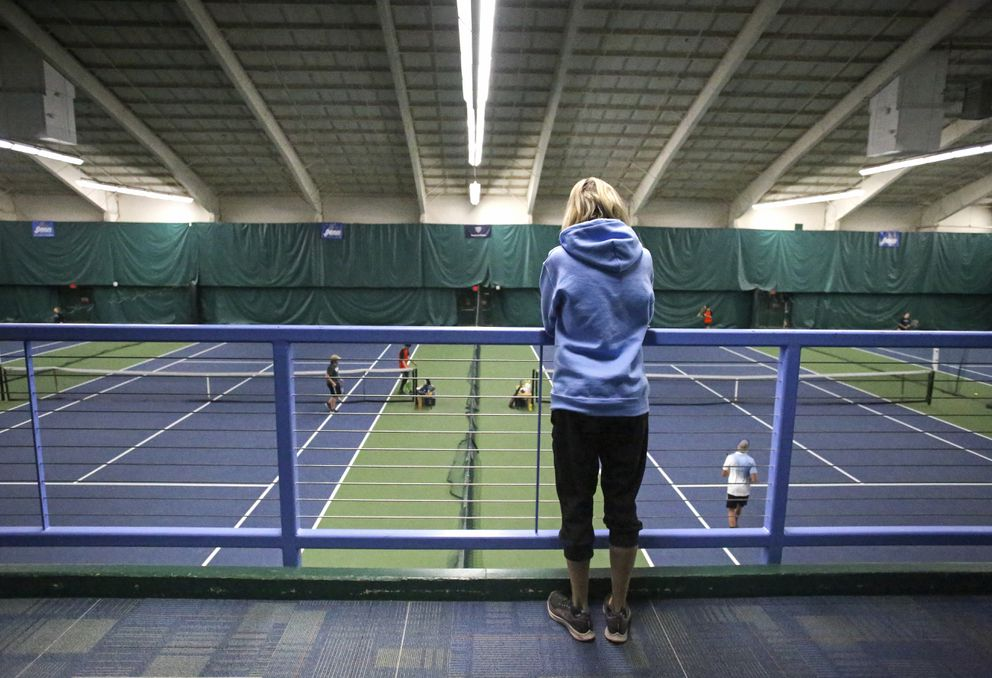Chugiak High School's assistant tennis coach Amy Belmear watches the matches from a balcony at The Alaska Club East. Attendance at the matches is limited. (Emily Mesner / ADN)