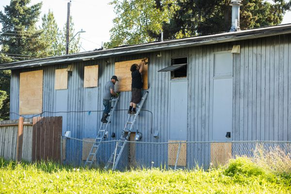 Contractors board up a fire-damaged fourplex Tuesday, Sept. 4, 2018 in Mountain View. The municipality is working with Wellsfargo, which owns the building, to board it up and clean the property. (Loren Holmes / ADN)
