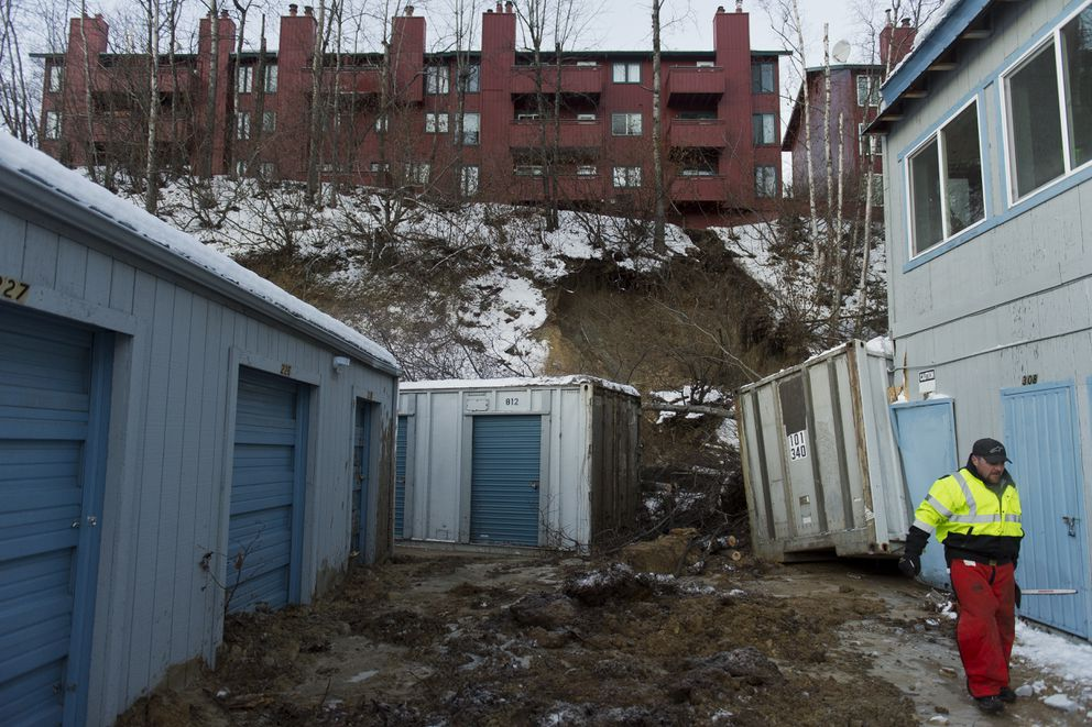 Devin Hueser of American Landscaping worked to clear brush in the area of a mudslide Tuesday morning. Mud slid from a Muldoon hill between the Victoria Hill Condos and Muldoon Mini Storage on Monday morning. A waterline broke beneath the condos prior to the slide. Photographed January 15, 2019. (Marc Lester / ADN)