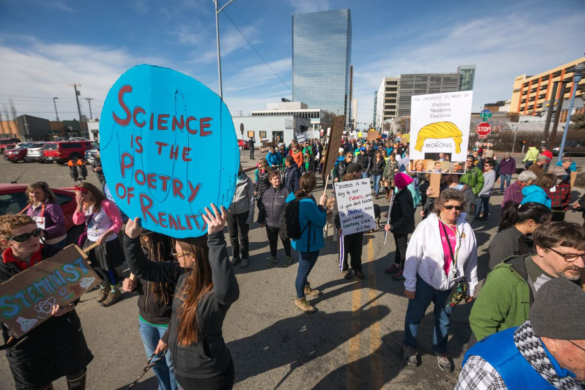 """Andrea Gilstad holds a sign that says """"science is the poetry of reality"""" during the March for Science on Earth Day, April 22. (Loren Holmes / Alaska Dispatch News)"""
