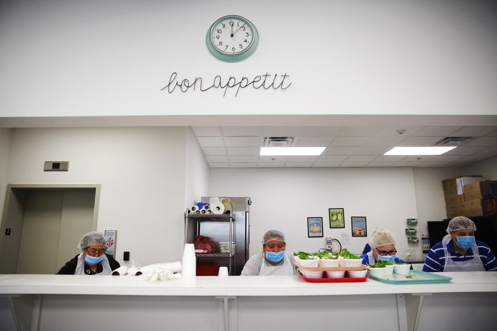 In this March 4, 2020, photo, the staff at Little Havana Activities and Nutrition Centers of Dade County, Inc., prepares lunch for seniors in Miami. The new coronavirus is posing a special challenge for nursing homes and other facilities that provide care for the elderly. (AP Photo/Brynn Anderson)