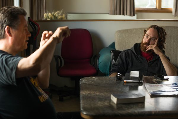 Recovering addict Eric Garcia, left, talks to artist David Pettibone Tuesday, Aug. 28, 2018 at Garcia's group home in north Anchorage. Garcia and Pettibone are collaborating on a mural that will address the problem of adverse childhood experiences. (Loren Holmes / ADN)