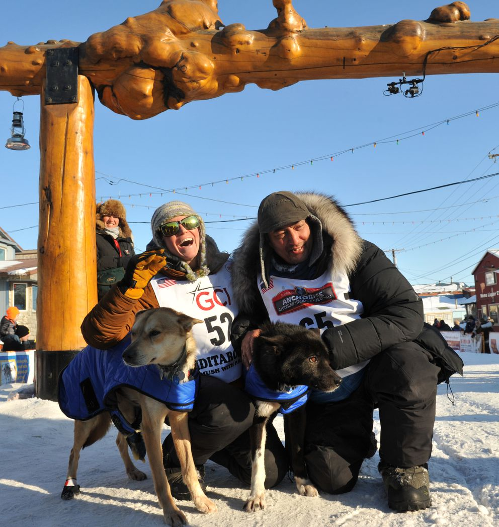 Mushers Katherine Keith and her fiancé John Baker and Katherine's leaders Blondie and Katherine pose for photographs after crossing the Iditarod finish line together in Nome on March 15, 2017. Baker finished 1 second ahead of Keith. (Bob Hallinen / ADN)