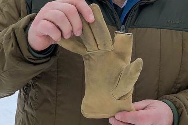Iditarod Race Marshal Mark Nordman holds up a 4 1/2 fingered glove Wednesday, March 7, 2018 in Takotna. He said he was given the glove by a snowmachiner who picked it up on the trail before McGrath and that he was going to deliver it to Mitch Seavey. (Loren Holmes / ADN)