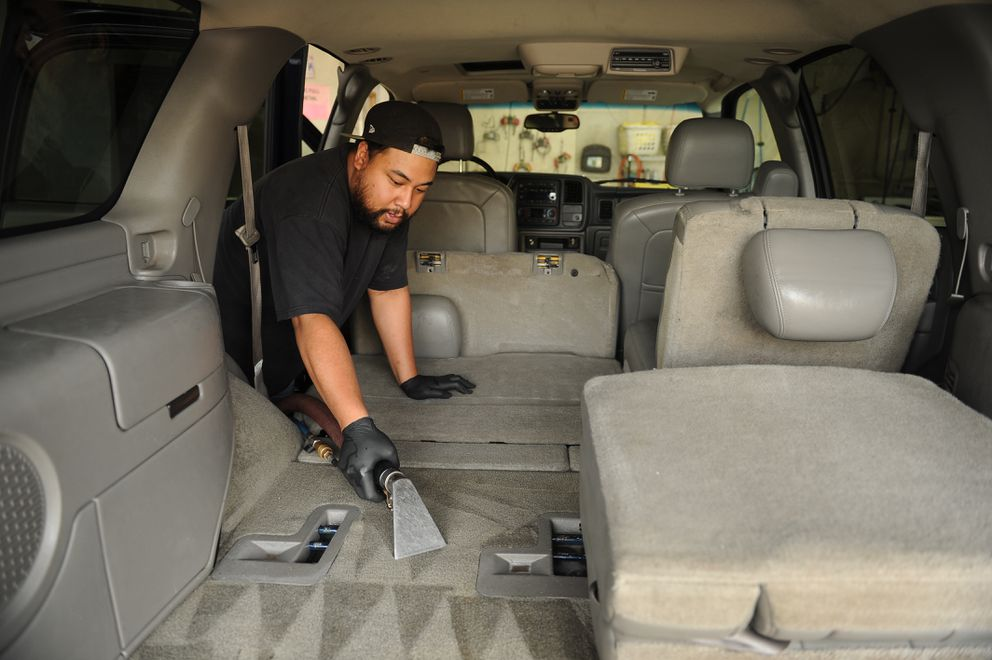 Curtis Pama uses an extractor after shampooing the interior of a Chevy Tahoe at The Purple Turtle auto detailing shop. The shop has been cleaning many recovered stolen cars. (Bob Hallinen / ADN)