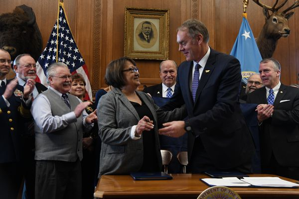 Della Trumble of King Cove Corp. and Interior Secretary Ryan Zinke at the signing a deal Monday, Jan. 22, 2018, in Zinke's Washington office aimed at advancing construction of a road through the Izembek National Wildlife Refuge on the Alaska Peninsula, from King Cove to Cold Bay. King Cove Mayor Henry Mack is to the left of Trumble. Also present for the signing were Alaska Gov. Bill Walker, center, and Alaska's congressional delegation. (U.S. Dept. of the Interior)