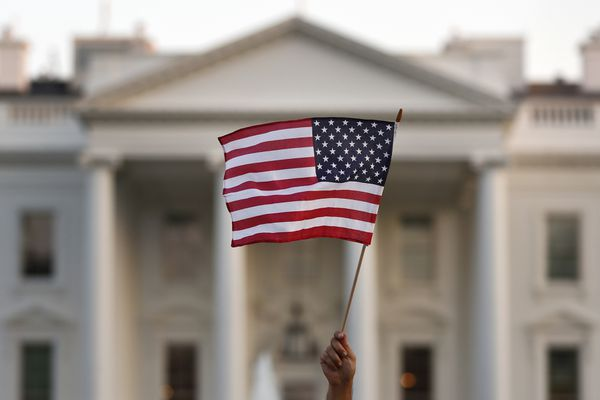 FILE - In this Sept. 2017 file photo, a flag is waved during an immigration rally outside the White House, in Washington. President Donald Trump has touted the creation of an office created to help victims of crimes committed by people in the U.S. illegally. But most of the people calling the Trump administration hotline aren't calling to get information. They are calling to report their neighbors, colleagues or strangers who they suspect are in the country illegally. (AP Photo/Carolyn Kaster)