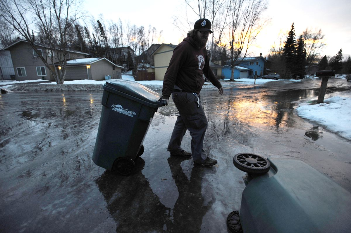 Bob Savello retrieves his garbage can after it was blown down an icy East Anchorage street during the windstorm on Monday morning. (Bill Roth / ADN)