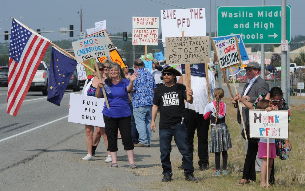 Citizens who support a full PFD waved to motorists on the Parks Highway before the legislative special session was held at Wasilla Middle School on Monday, July 8, 2019. (Bill Roth / ADN)