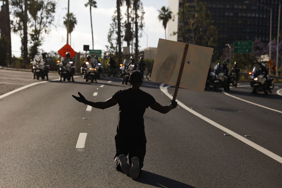 A man kneels on the street in front of police officers while chanting 'I can't breathe ' during a protest over the death of George Floyd, Friday, May 29, 2020, in Los Angeles. Floyd died Memorial Day while in police custody in Minneapolis. (AP Photo/Jae C. Hong)