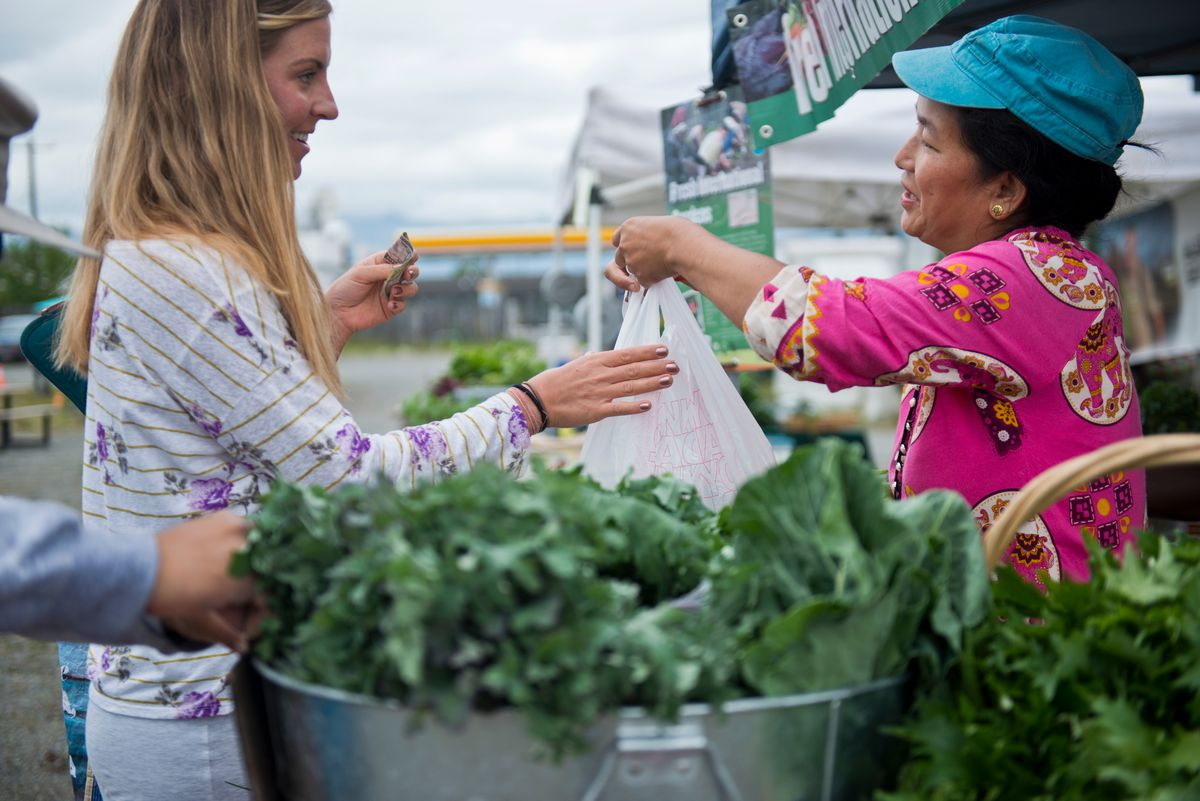 Chandra Subba sells to a customer at the Fresh International Gardens stand at the market. (Marc Lester / Alaska Dispatch News)