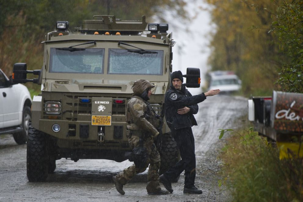 Anchoragepolice stage neara home on Ginami Street on Thursday morning, where a Hillside resident opened fire on a tree-trimming crew Wednesday morning and then on police later in the day. (Marc Lester / Alaska Dispatch News)
