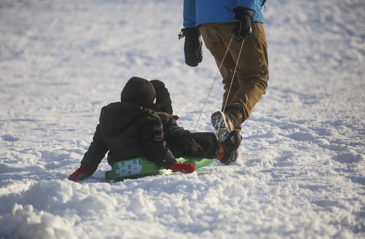 Thomas and Samuel Kushner ride in a sled, pulled by Adam Kushner, to play in the snow outside Inlet View Elementary School in Anchorage on Nov. 9, 2020. (Emily Mesner / ADN)