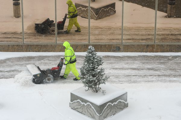 A worker sweeps the sidewalks in downtown Anchorage during the snowstorm on Monday, Feb. 26, 2018. (Bill Roth / ADN)