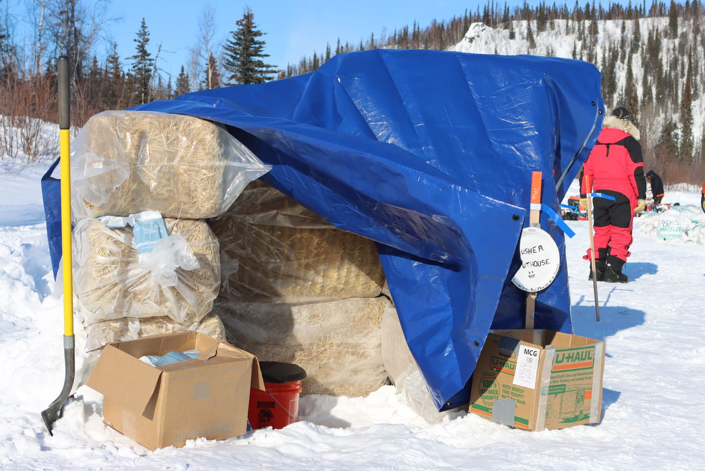 An outhouse set up for mushers at the barebones Ophir checkpoint, consists of a bucket, tarp, and straw bales on Wednesday. (Zachariah Hughes/for ADN)
