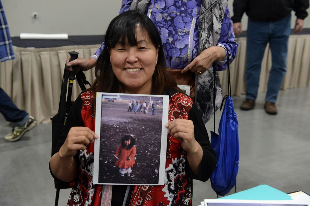 Elvina Lincoln holds a photograph of herself as a 3-year old in Anaktuvuk Pass, AK at the Anchorage Museum booth at AFN. (Bob Hallinen / ADN)