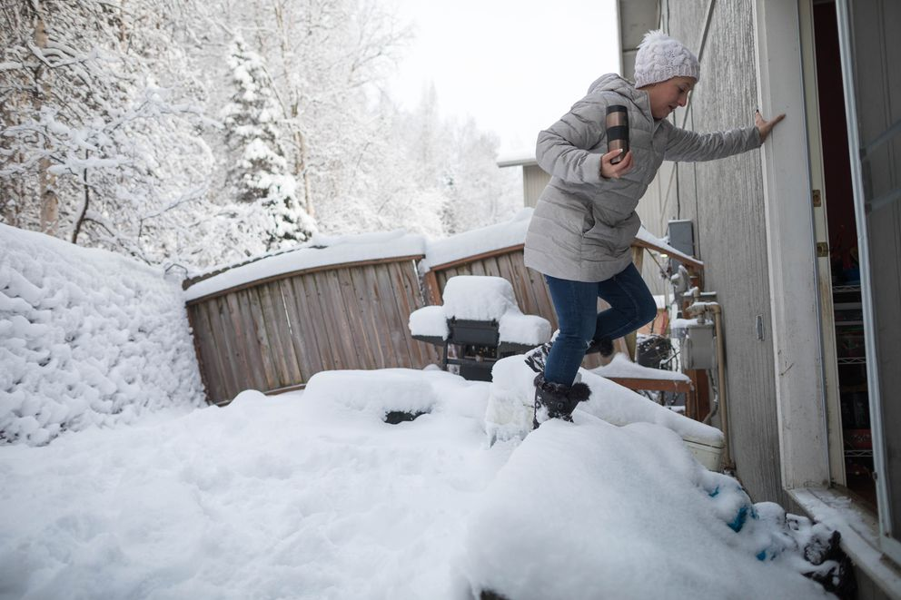Mallory Valentine steps over a broken deck in her parents' backyard in Eagle River on Thursday. The home and seven others in the neighborhood were red-tagged, deeming them unsafe to occupy, by the municipality. (Loren Holmes / ADN)