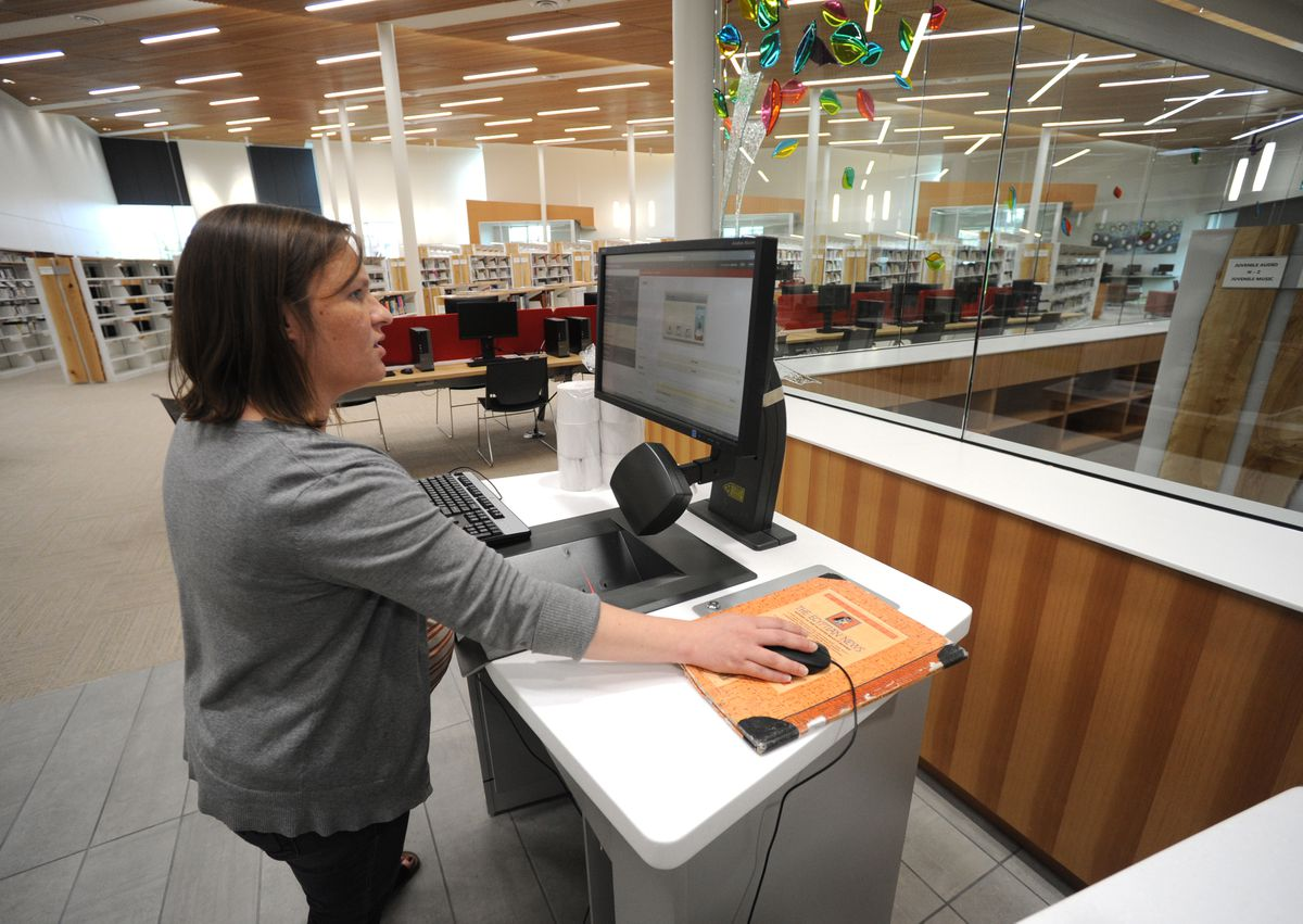 User services librarian Aly Brown sets up self-checkout stations in the new Wasilla Public Library on Wednesday. (Bill Roth / Alaska Dispatch News)