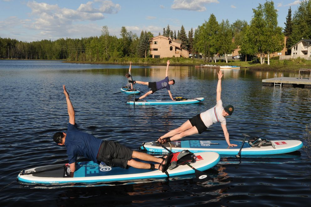Hailey Hosken, right, practices yoga during a stand-up paddleboard lesson. (Bill Roth / Alaska Dispatch News)​