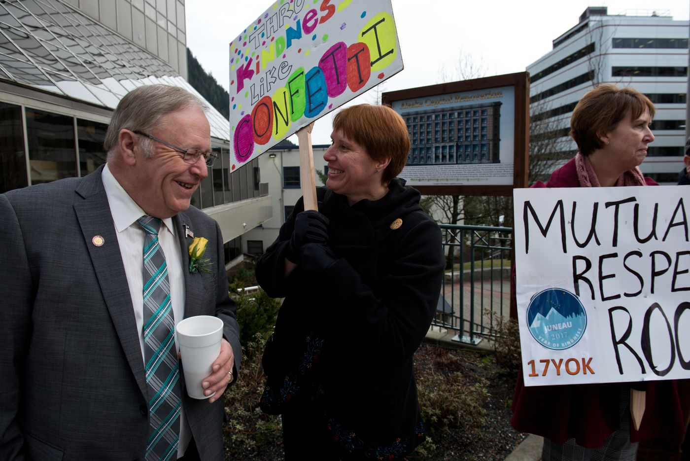 """Rep. Mike Chenault, R-Nikiski, talks with Kris Sell, a Juneau police lieutenant, outside the Capitol. Sell, holdinga sign that says """"Spread kindness like confetti,"""" participated in a rally for encouragement of lawmakers, part of the """"Year of Kindness"""" campaign."""