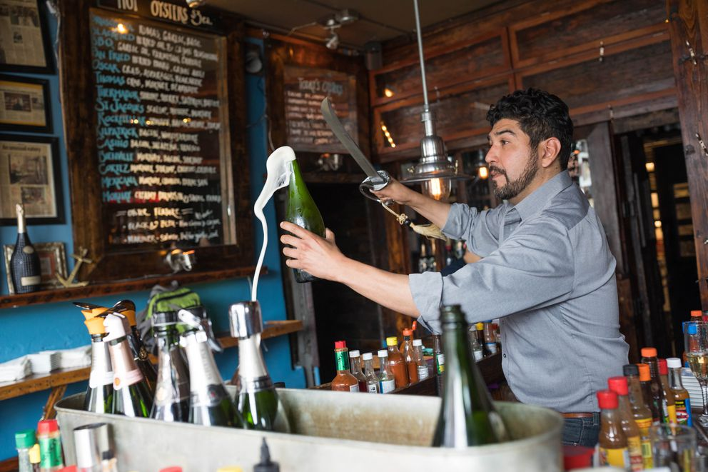Bubbly Mermaid Champagne and Oyster Bar owner Apollo Naff sabers a bottle of champagne at the bar. (Loren Holmes / ADN)