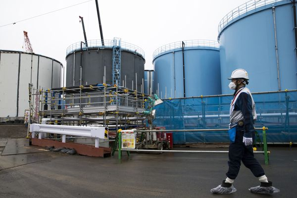 An employee passes storage tanks for contaminated water at Tokyo Electric Power Co.'s Fukushima Dai-ichi nuclear power plant in Okuma, Fukushima, Japan, on Feb. 23, 2017. MUST CREDIT: Bloomberg photo by Tomohiro Ohsumi