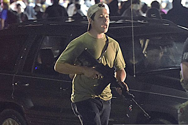 FILE - In this Tuesday, Aug. 25, 2020 file photo, Kyle Rittenhouse carries a weapon as he walks along Sheridan Road in Kenosha, Wis., during a night of unrest following the weekend police shooting of Jacob Blake. The way his lawyers tell it, the teenager wasn't a scared, gun enthusiast in over his head when he fatally shot two protesters. He was a courageous defender of liberty, a patriot exercising his right to bear arms amid chaos in the streets. But some legal experts say Rittenhouse's lawyers are taking big risks by turning a fairly straightforward self-defense case into a sweeping political argument that mirrors the law-and-order re-election campaign of President Donald Trump. (Adam Rogan/The Journal Times via AP)