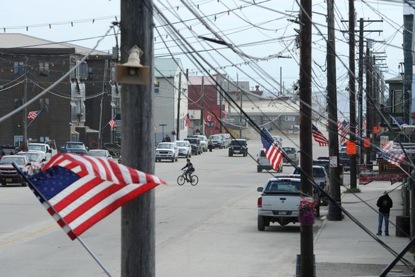 A bicyclist crosses Front Street in Nome on Friday, June 28, 2019. The U.S. Flags lining Front Street have been up since Memorial Day as residents get ready to celebrate Independence Day with a parade on the 4th of July. (Bill Roth / ADN)