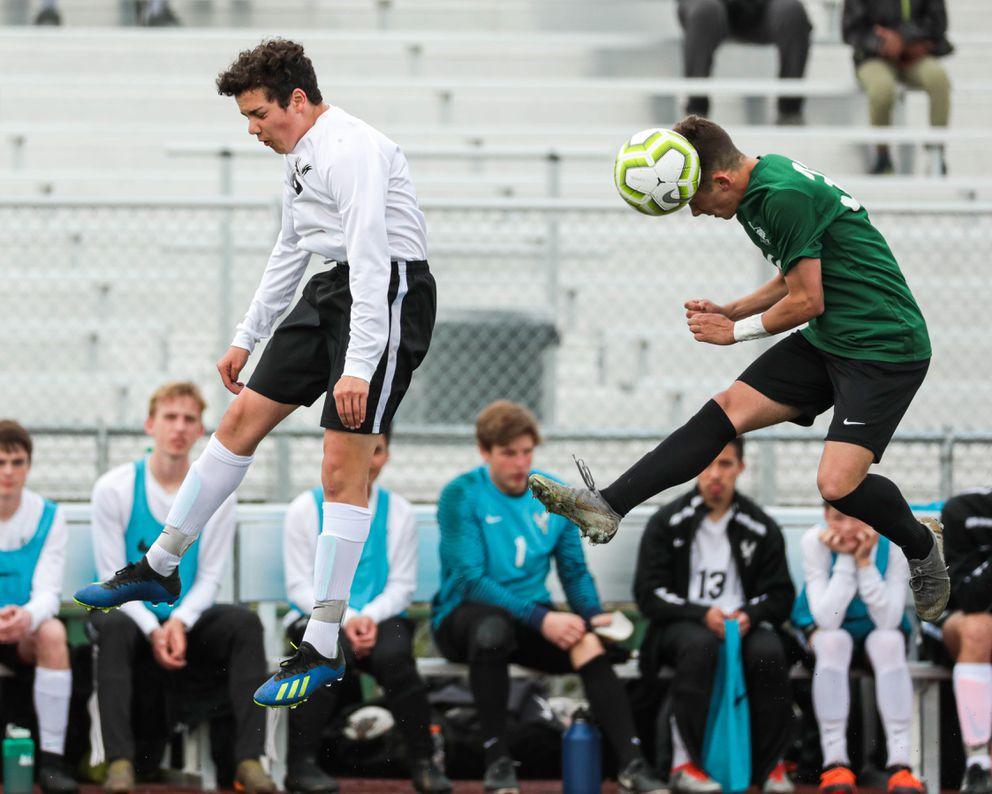 Colony sophomore Connor Friesen heads the ball while West freshman Mikhail Turchaninov jumps Saturday, May 25, 2019 during the state high school soccer match at Service High. (Loren Holmes / ADN)