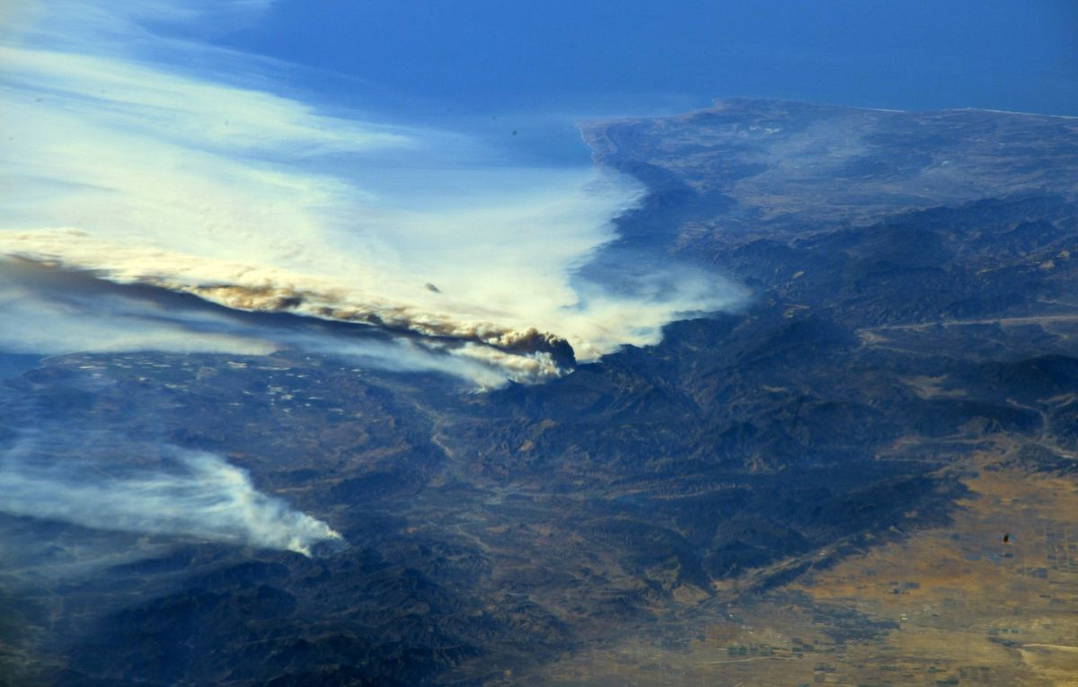 A photo taken Thursday from the International Space Station and moved on social media by astronaut Randy Bresnik shows smoke rising from wildfires in Southern California. Courtesy @AstroKomrade/NASA/Handout via REUTERS