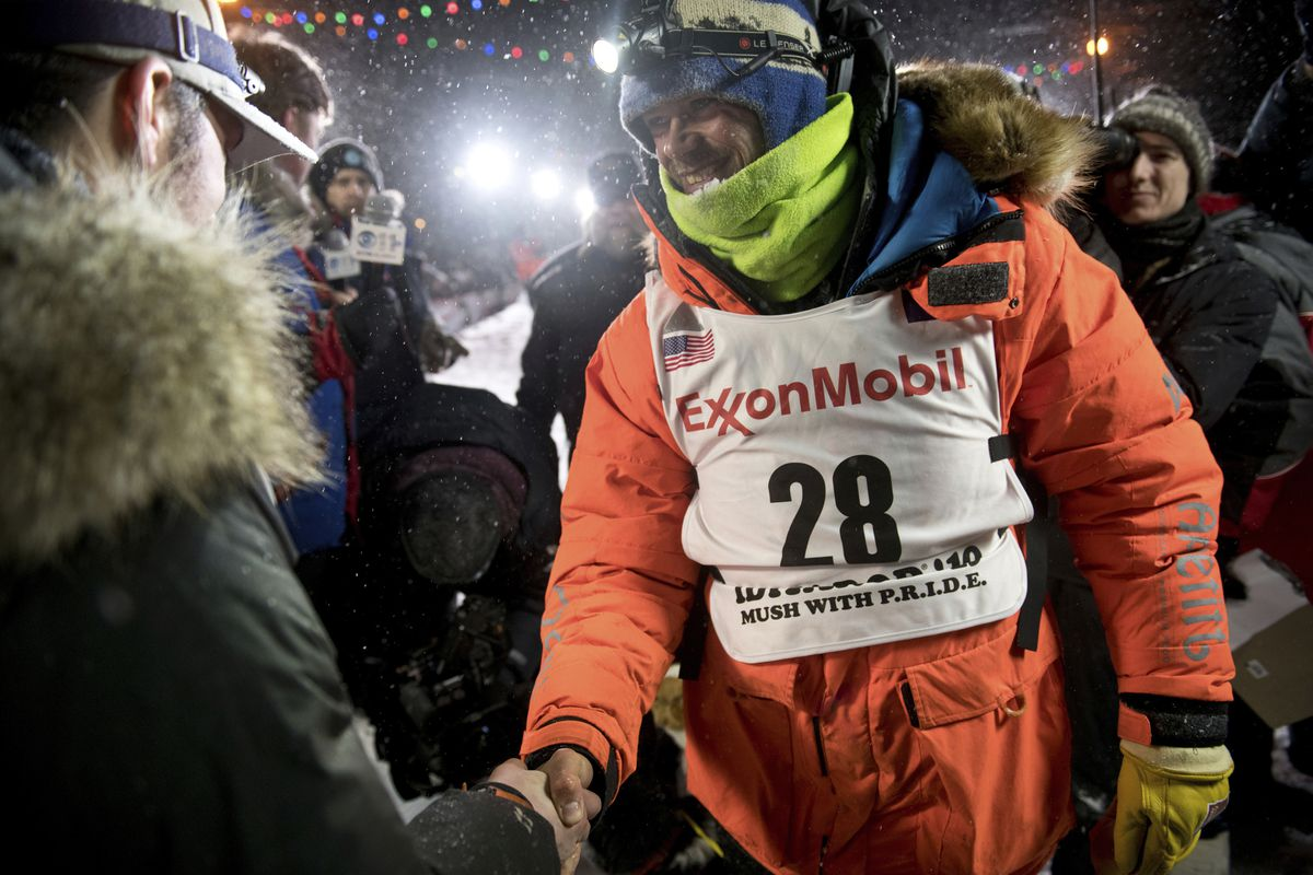 In this March 13, 2019, file photo, Joar Leifseth Ulsom, right, wearing a bib with ExxonMobil lettering on it, congratulates Peter Kaiser on his win in the Iditarod Trail Sled Dog Race in Nome. (Marc Lester / ADN archive)