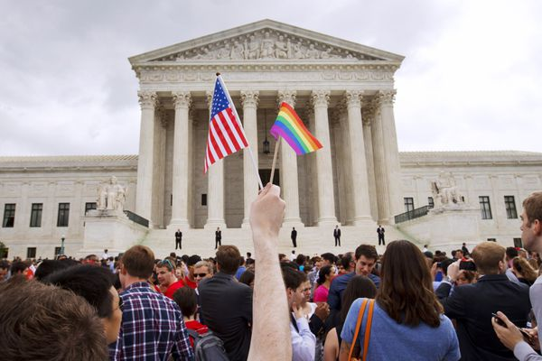 FILE - In this June 26, 2015 file photo, a man holds a U.S. and a rainbow flag outside the Supreme Court in Washington after the court legalized gay marriage nationwide. Court documents show the state of Alaska for years maintains a discriminatory policy that denied some same-sex spouses benefits by wrongly claiming gay marriage was not recognized in Alaska, long after courts ordered they be recognized. (AP Photo/Jacquelyn Martin, File)