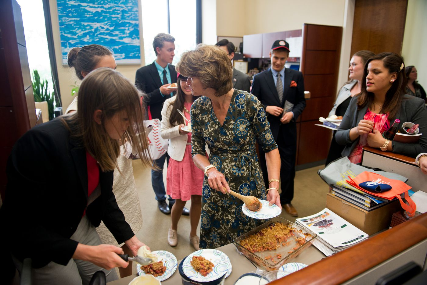 Sen. Lisa Murkowski dishes up rhubarb crisp to her interns on their last day working with her office on Thursday, June 25, 2015. Twenty recent high school graduates spend one month interning with Murkowski each summer, ten at at time. (Marc Lester / Alaska Dispatch News )