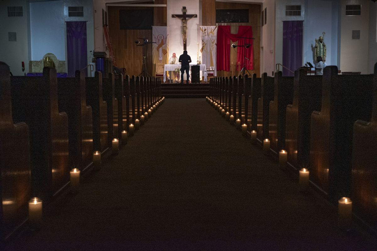 In this April 11, 2020, file photo, a person films pastor Nicolas Sanchez, center left, celebrating Easter Vigil Mass at his church decorated with candles and pictures sent by his parishioners attached to their pews at St. Patrick Church in North Hollywood, Calif. (AP Photo/Damian Dovarganes, File)