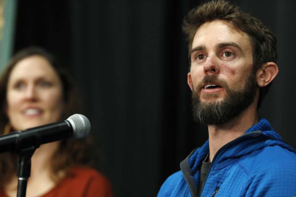 Travis Kauffman responds to questions during a news conference Thursday, Feb. 14, 2019, in Fort Collins, Colo., about his encounter with a mountain lion while running a trail just west of Fort Collins last week. Kaufman's girlfriend, Annie Bierbower, looks on at left. (AP Photo/David Zalubowski)
