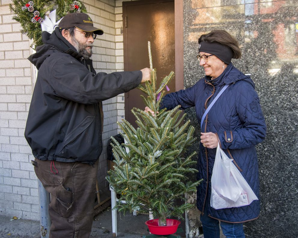 Tom Gilmartin hands a small Christmas tree to Lisa Horner, of Chelsea, at the Gilmartin's Christmas tree stand on the corner of West 22nd Street and 9th Avenue in New York City. (Taylor Balkom / taylorbalkom.com)