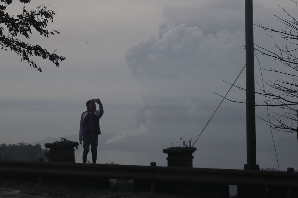 A man takes a selfie as Taal Volcano as it spews ash on Monday Jan. 13, 2020, in Tagaytay, Cavite province, south of Manila, Philippines. The small volcano near the Philippine capital that draws tourists for its picturesque setting in a lake erupted with a massive plume of ash and steam Sunday, prompting the evacuation of tens of thousands of people and forcing Manila's international airport to shut down. (AP Photo/Aaron Favila)